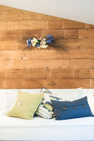 Shiplap wall above bed.