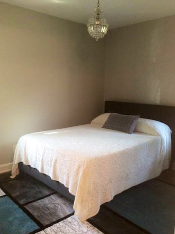 Full bedroom offers amazing Nectar bed with pillows and a vintage crystal chandelier.