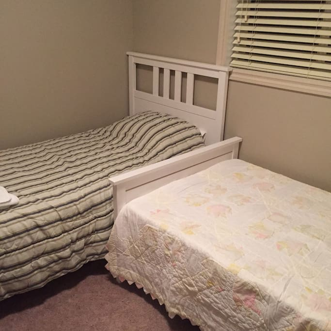 Second bedroom has two twin beds, bedside table, and lamp.