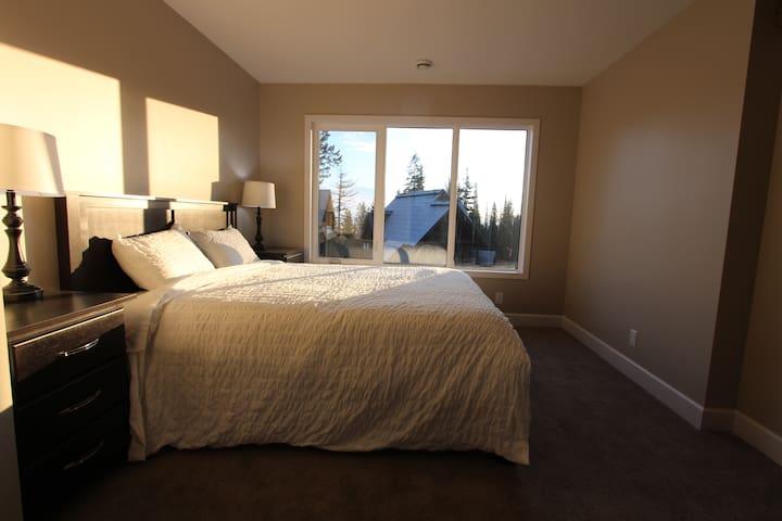 Upstairs bedroom w/ ensuite, queen bed, closet, flatscreen TV and valley views.