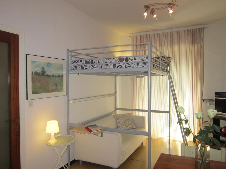 Soggiorno con letto matrimoniale a soppalco. Living room with a king size loft bed