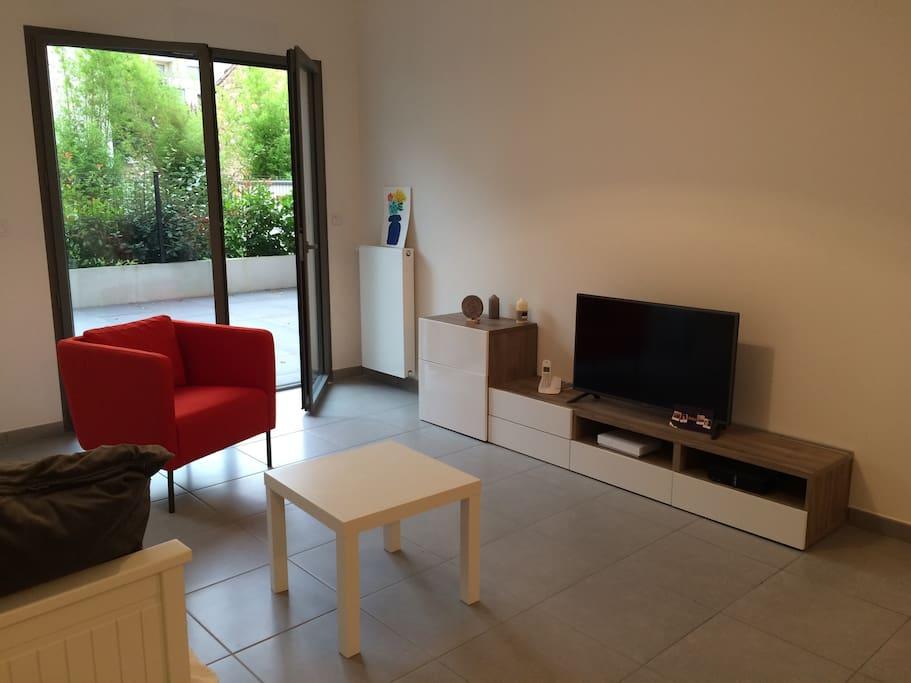 Salon lumineux avec box, télévision