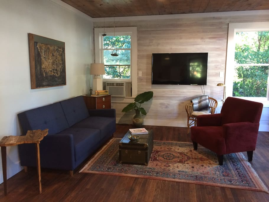 Main living area is open to the kitchen and includes a foldout couch, flatscreen TV and plenty of natural light.