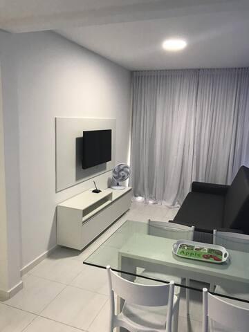 Sala confortável equipada com Smartv de 40 polegadas, sofá cama, mesa de jantar, ventilador.