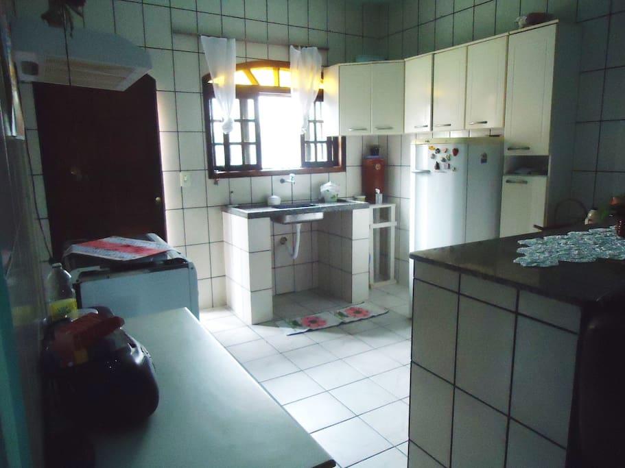 Cozinha equipada com fogão, geladeira, armários, talheres, pratos, panelas e outros utensílios