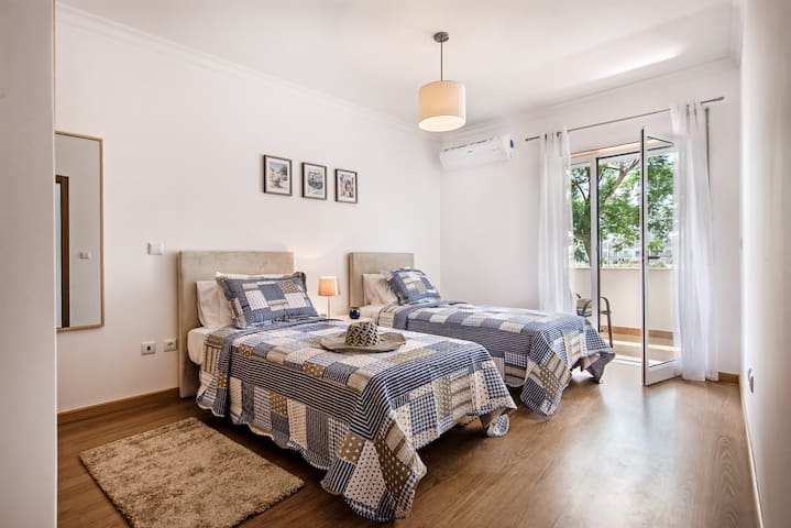 A smart and stylish twin bedroom with a balcony