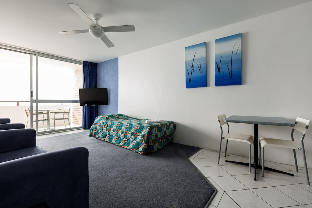 Large living area with 40 flat screen tv with large balcony doors opening onto large open balcony