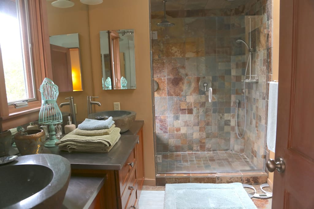 Huge sand stone waterfall shower, with a second shower head and stone bench, and a view of the woods. And two gorgeous geode stone sinks.