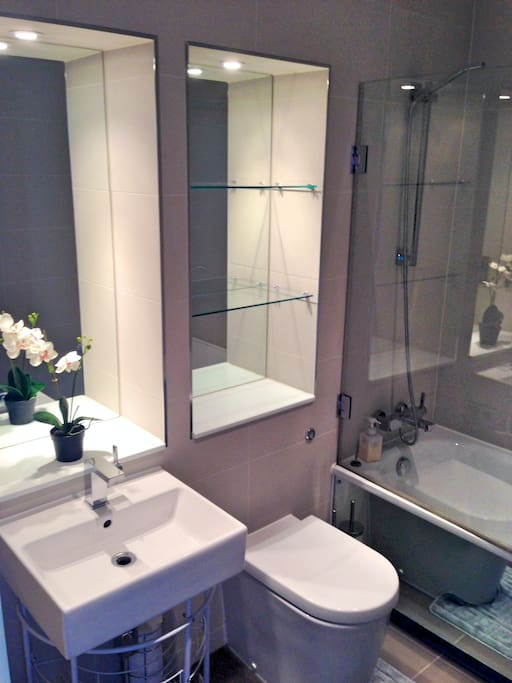 Your private luxury bathroom with toilet, sink, bathtub with shower, heated towel rail and shelves/storage space