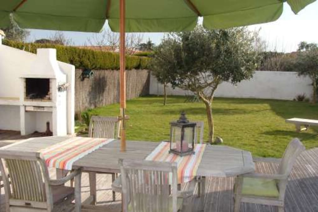 Grande terrasse en bois exposée plein sud avec barbecue et salon de jardin