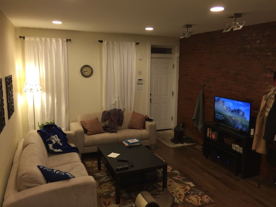 The living room has a sofa/love seat combo that face an entertainment center with a flat screen TV and blu ray player.