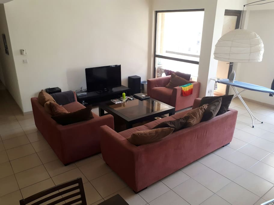 This is our super cosy living room with many TV channels and a dining area. There is access to the balcony from here and also space to dry and iron your clothes.