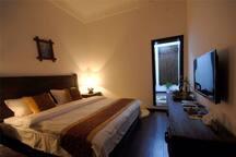 花园大床房:穿过花园进入房间,18平方米,落地玻璃窗,邻近大理古城最热闹的南城门。