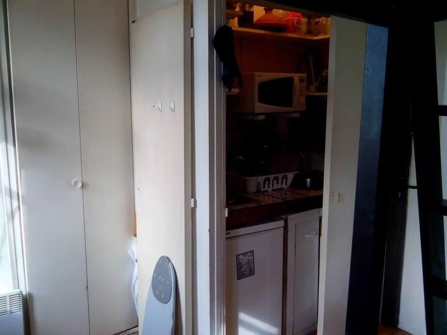 Espace de cuisine: plaques chauffantes micro-ondes, frigo, vaisselles et ustensile variés. Placard en face et bureau à gauche
