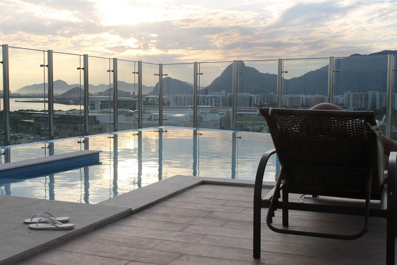 Edifício com piscina no terraço e vista para a Lagoa da Barra, montanhas e local das Olimpíadas.