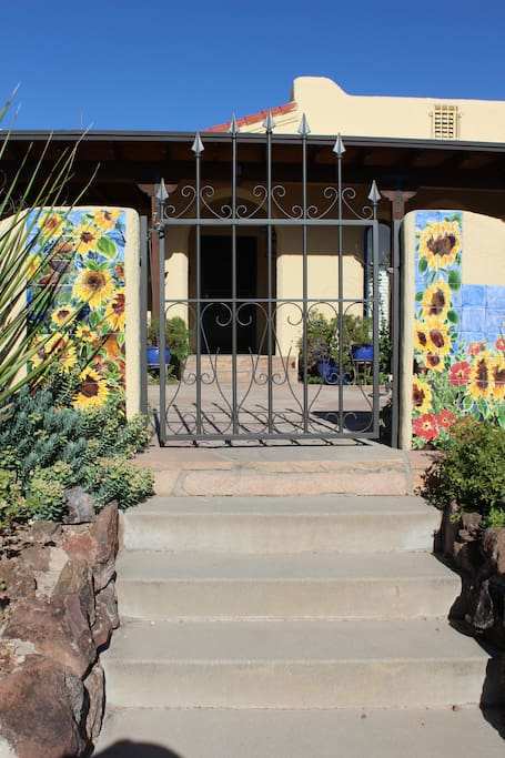View from the street through the gated front area.  Handpainted tiles of sunflowers on the front wall.