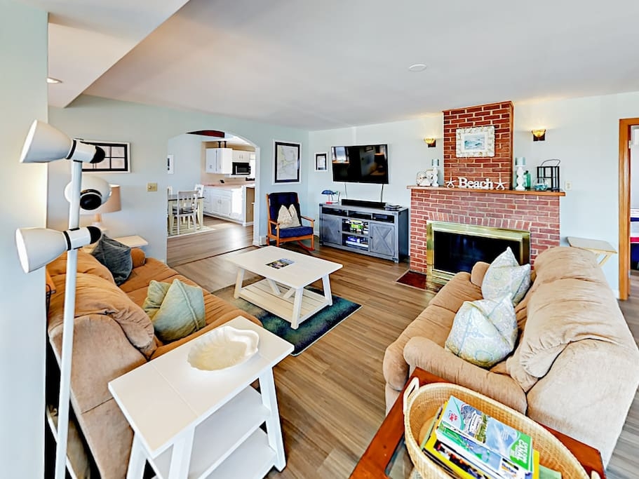 """The spacious open concept living room offers a comfy couch, matching love seat and a large rocking chair, where you can relax in front of the 55"""" HDTV with cable and Netflix access."""