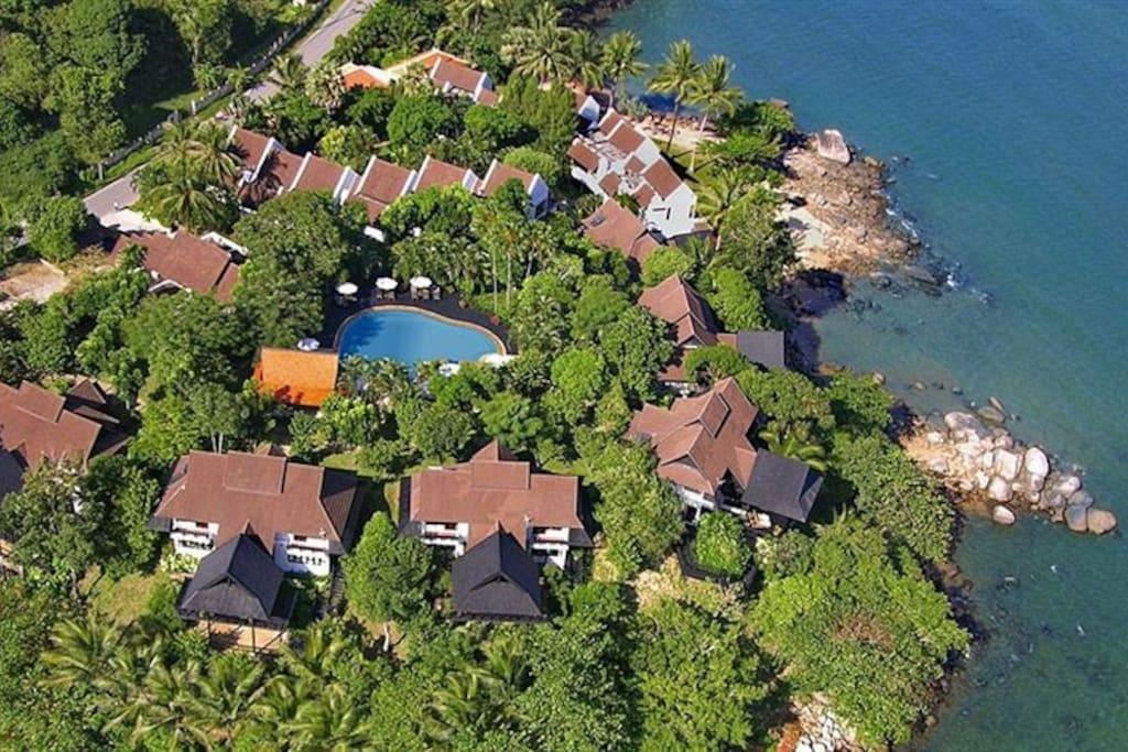 An aerial view of the estate on which the villa is located. The villa is dead center on the left, overlooking the small inlet.