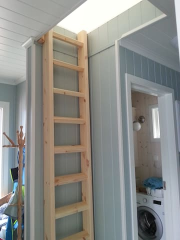 """Ladder up to the separate sleeping loft above the bathroom/enterace . It can be drawn away from the wall for an easier climb.  A hatch om wheels can be rolled over the opening in the ceiling so there is a kind of  """"door"""" if you want."""