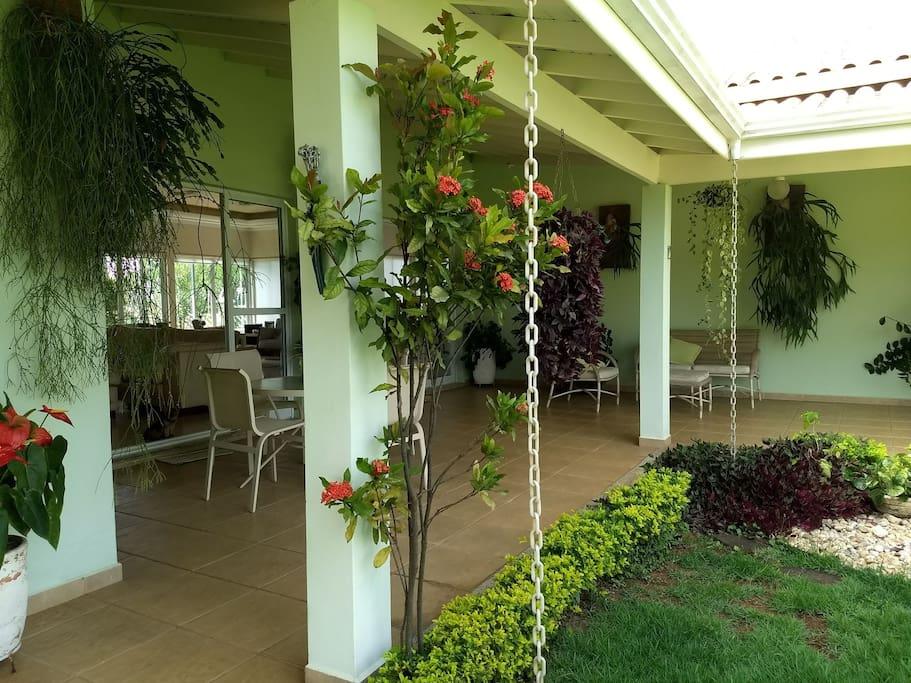 Varanda coberta, lindamente ajardinada, ampla e entorno de toda a casa. Com mesa, cadeiras, sofás e 4 redes de descanso.