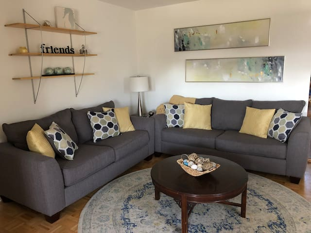 A luxurious and comfy gathering space; a flat screen TV and large leather chair on the opposite wall