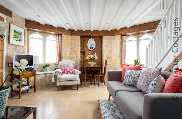 The characterful living room has flagstone flooring and exposed Cotswold stone walls
