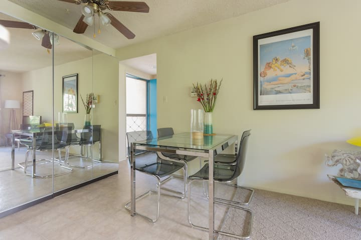 Dining area with fashionable glass topped table and comfortable chairs for pleasant meal enjoyment while looking at the lovely view through the living room glass doors or the reflected view from the mirrored locked closets' doors.