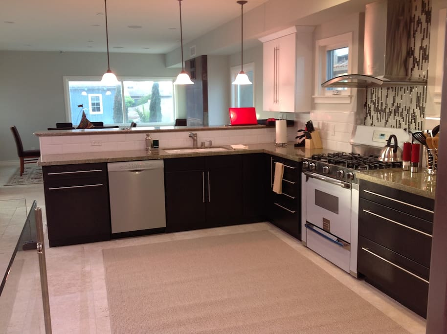 Kitchen with bar counter dining area, and separate sitting area with large flat screen TV.