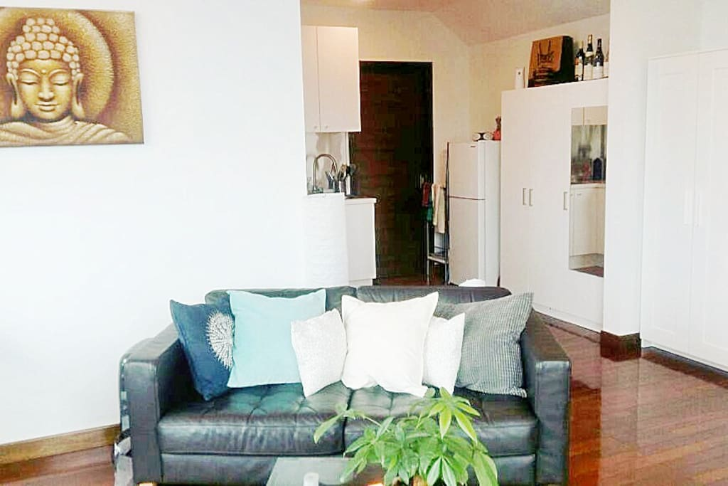 Studio apartment with kitchenette, sitting area inside.