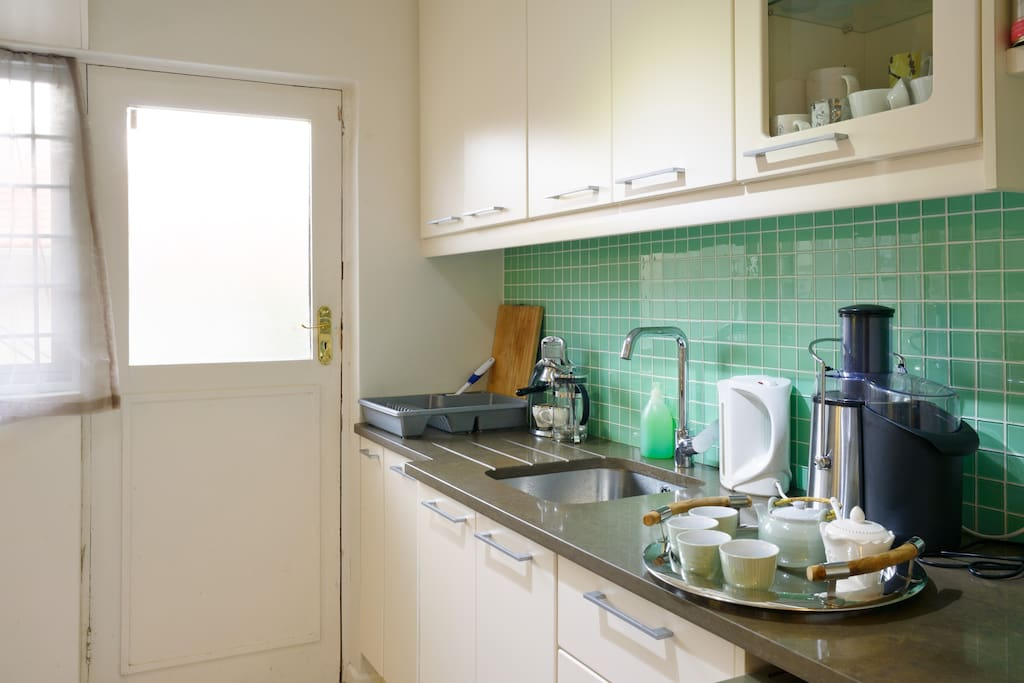 the clean modern kitchen includes a dishwasher and a retro presso (coffee maker)
