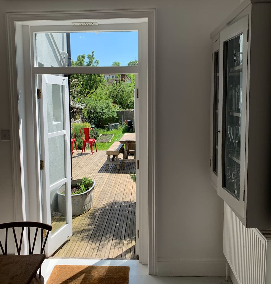 Our spacious lower ground floor kitchen leads directly onto a decked area with wooden seating - perfect for meals al fresco - and our idyllic garden with lawn, flower beds and fruit trees.
