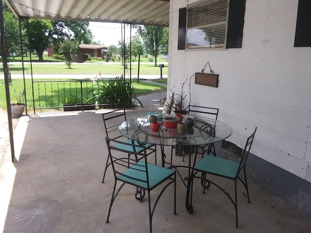 The covered patio has plenty of seating around the cabin.