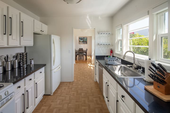 Clean spacious kitchen equipped with items necessary to whip up a meal.