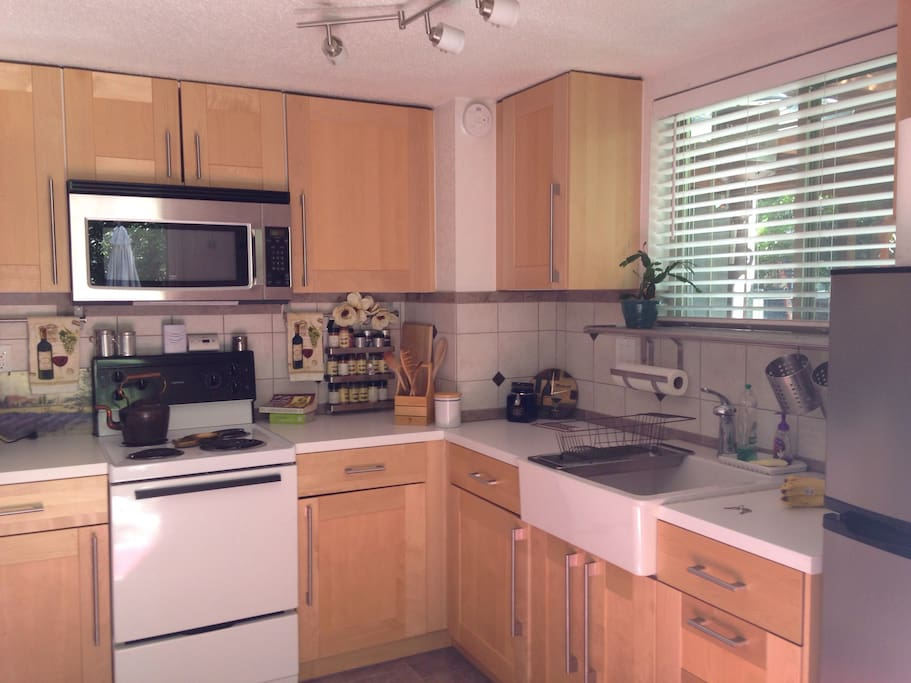 Large, newly remodeled kitchen open to the living area, w microwave and full refrigerator (stocked with many condiment essentials).