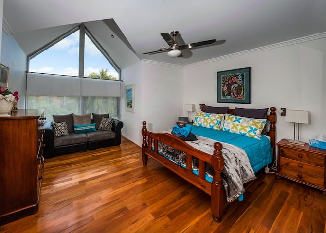 Large bedroom -queen size bed, bedside tables, chest of drawers, lounge, built-in wardrobe and safe.