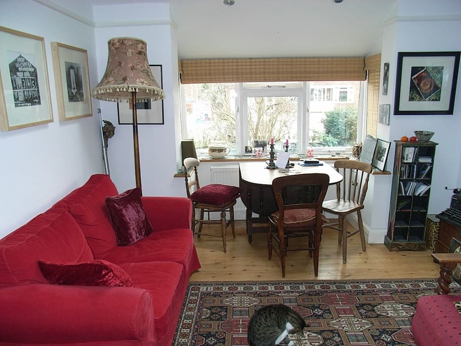 Spacious airy sitting room with dining area looking over front garden.
