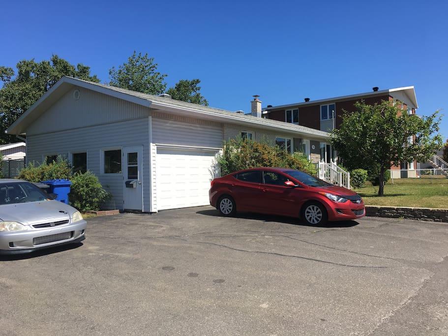 L'accès au logement se fait par la porte sur le côté du garage.