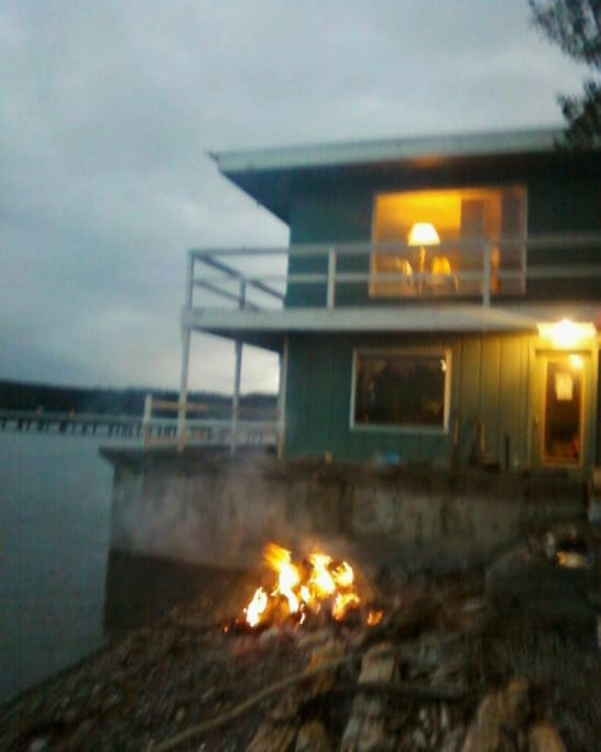 A fire on the beach in front of the house. The first floor is our guest  rental area.