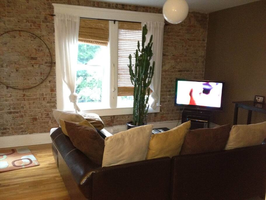 Living room with wrap around couch, natural light and TV.