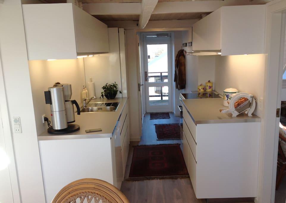 Velindrettet køkken med komfur, kaffemaskine, opvaskemaskine m.v.