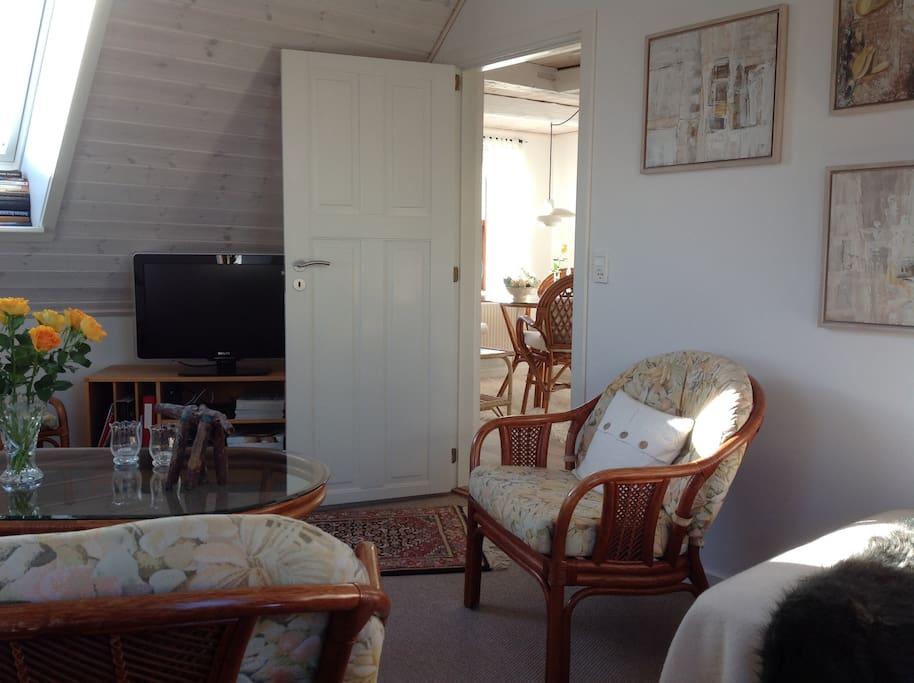 Opholdsstue med 2 senge, sofa, stole, TV m.v.