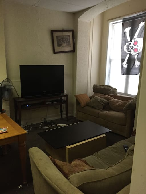 A living room with multiple couches, a TV with cable access, and tables and shelving (not shown)