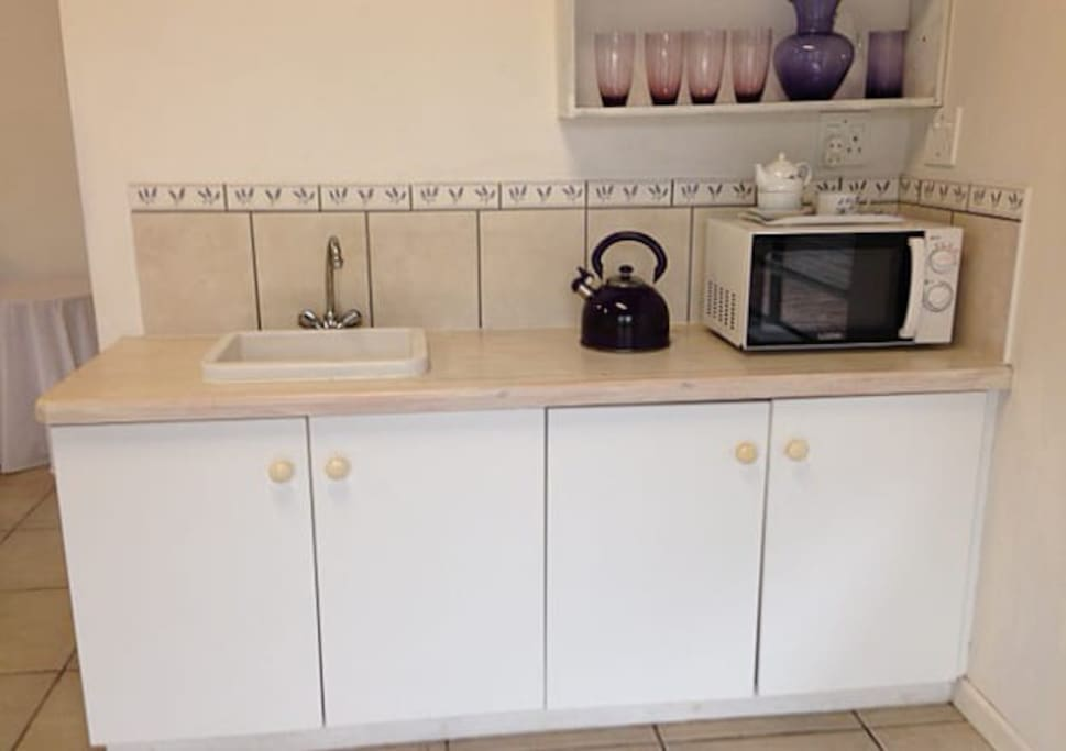 Kitchenette with small fridge, frying pan and microwave oven