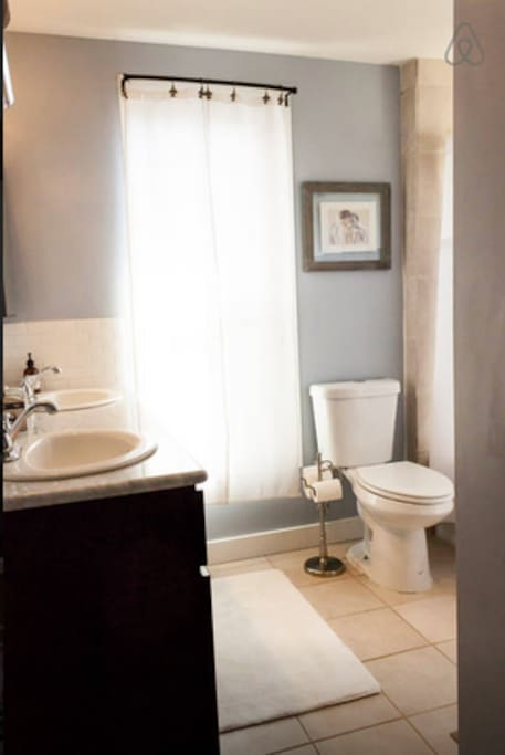 Double sink in shared bathroom, shower and tub around the corner next to duel flush toilet.