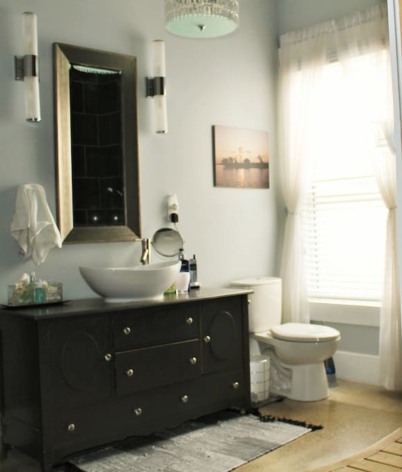 Funky full bathroom with open concept shower and laundry will leave you refreshed and relaxed.
