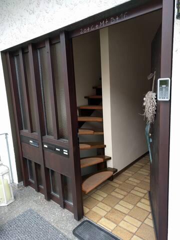 Der Eingangsbereich. Rechts ist das Türschloss zu sehen, welches per PIN Code die Tür öffnet. Links die Treppe hoch geht es zur Wohnung.