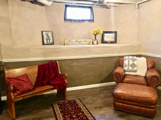Comfortable sitting area with leather armchair and cozy blankets!
