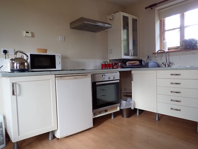 Kitchen area with microwave, toaster, kettle, electric oven, gas hob, fridge and sink.
