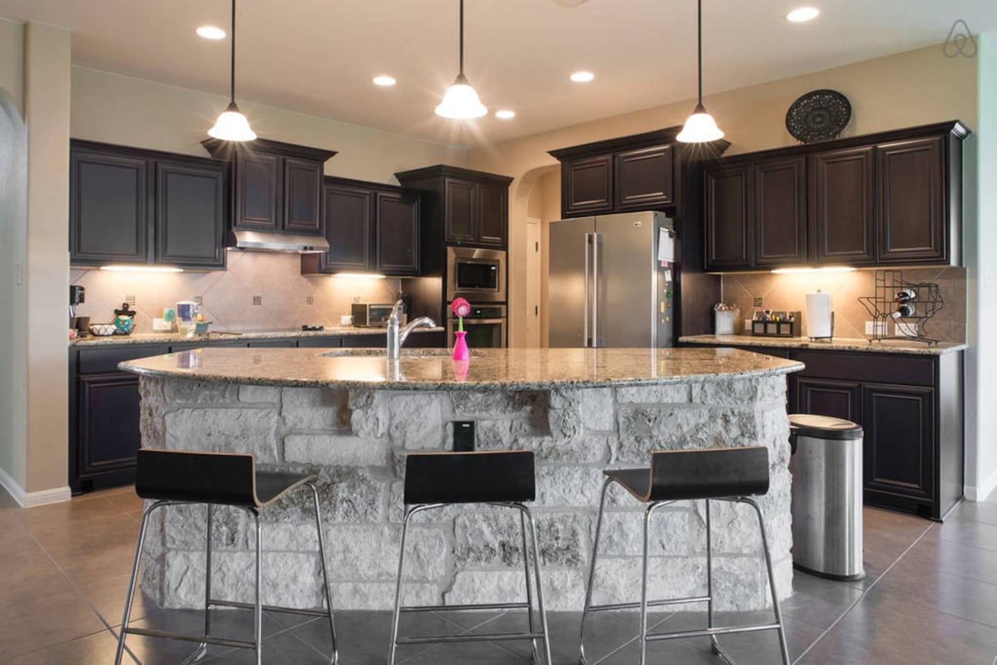 Kitchen (microwave & fridge access only), stone island w/ granite counter tops and bar stools.