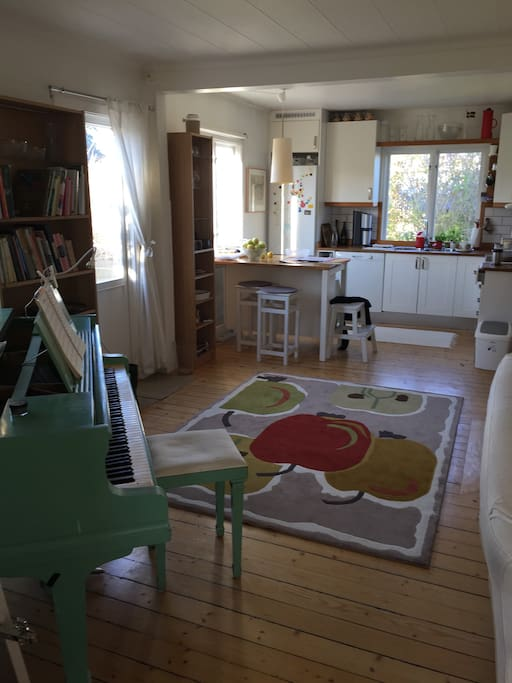 The livingroom and the kitchen also includes a grand piano.